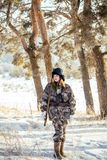 Female hunter in camouflage clothes ready to hunt, holding gun a. Nd walking in forest. hunting and people concept stock photography