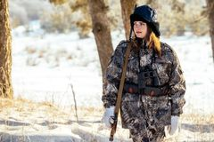 Female hunter in camouflage clothes ready to hunt, holding gun a royalty free stock photos