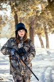 Female hunter in camouflage clothes ready to hunt, holding gun a. Nd walking in forest. hunting and people concept royalty free stock image