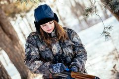 Female hunter in camouflage clothes ready to hunt, holding gun a. Nd walking in forest. hunting and people concept royalty free stock images