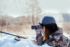 Female hunter in camouflage clothes ready to hunt, holding gun a royalty free stock photo