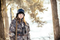 Female hunter in camouflage clothes ready to hunt, holding gun a. Nd walking in forest. hunting and people concept stock image
