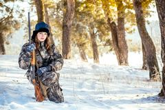 Female hunter in camouflage clothes ready to hunt, holding gun a. Nd walking in forest. hunting and people concept stock photo
