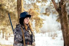 Female hunter in camouflage clothes ready to hunt, holding gun a. Nd walking in forest. hunting and people concept royalty free stock photography