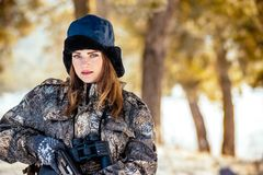 Female hunter in camouflage clothes ready to hunt, holding gun a. Nd walking in forest. hunting and people concept royalty free stock photo