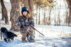 Female hunter in camouflage clothes ready to hunt, holding gun a. Nd walking in forest. hunting and people concept stock images