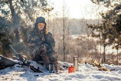 Female hunter preparing food with a portable gas burner in a win. Ter forest. Bushcraft, hunting and people concept royalty free stock image