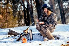 Female hunter preparing food with a portable gas burner in a win. Ter forest. Bushcraft, hunting and people concept Royalty Free Stock Photos