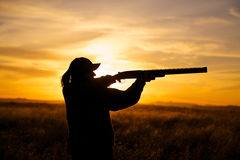 Female Hunter Shooting in Sunset. A female bird hunter silhoutted against a dramatic sunset with shotgun shouldered in shooting position stock image