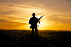 Hunter in Sunset. A female hunter silhoutted against a dramatic sunset with rifle Royalty Free Stock Photos