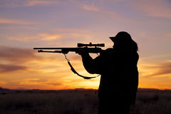 Female Hunter in Sunset. A female hunter silhoutted against a dramatic sunset with rifle royalty free stock images