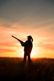 Female Hunter in Sunset. A female bird hunter silhoutted against a dramatic sunset with shotgun Royalty Free Stock Image