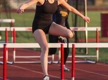 Female hurdling during track race stock image