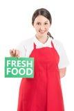 Female hypermarket worker holding fresh food sign Stock Photography