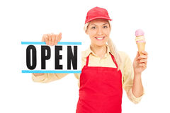 Female ice cream vendor holding an open sign Royalty Free Stock Images
