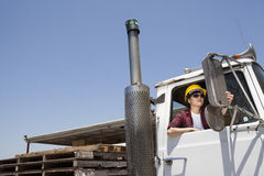 Female industrial worker adjusting mirror while sitting in logging truck Royalty Free Stock Photo