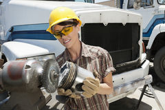Female industrial worker buffing a truck engine cylinder Royalty Free Stock Photos