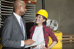 Female industrial worker looking at male inspector as he writes on clipboard Stock Image