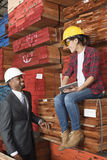 Female industrial worker and male engineer smiling while looking at each other at timber yard Royalty Free Stock Photo