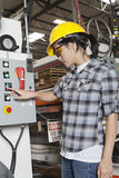 Female industrial worker operating manufacturing machine at factory stock image