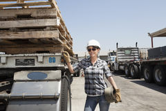 Female industrial worker standing by flatbed truck in timber yard Royalty Free Stock Photo