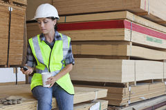 Female industrial worker taking break from work at timber yard Royalty Free Stock Images