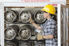Female industrial worker taking out propane cylinder Royalty Free Stock Image