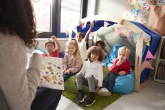 Female infant school teacher sitting on a chair showing a book to a group of children sitting on bean bags in a comfortable corner royalty free stock images