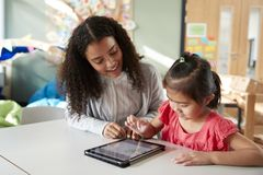 Female infant school teacher working one on one with a Chinese schoolgirl, sitting at a table in a classroom using a tablet comput. Er, close up stock photos