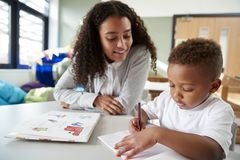 Female infant school teacher working one on one with a young schoolboy, sitting at a table writing in a classroom, front view, clo stock photos