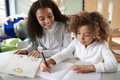 Female infant school teacher working one on one with a young schoolgirl sitting at a table writing in a classroom, front view, clo stock images