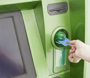Female inserts a plastic card in the ATM. Female inserts a plastic card in the green cash machine Royalty Free Stock Photo