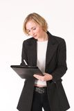 Female inspector. In suit with ledger in hand, writing Royalty Free Stock Photos