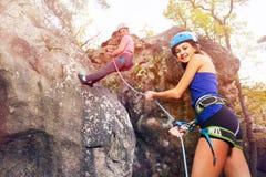 Instructor belaying girl rock climbing outdoors stock photography