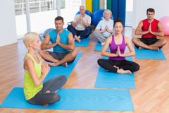 Female instructor with class meditating at gym. Full length of female instructor with class meditating with hands joined at gym Stock Images
