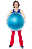 Female instructor displaying pilates ball used in gym Stock Image