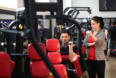 Female instructor explaining to a man how to workout Stock Photos