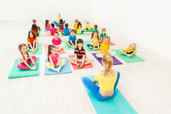 Female instructor giving yoga class for kids. Female instructor giving yoga class for 5-6 years old kids in light exercise room stock images