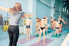 Instructor and group of children doing exercises. Female instructor and group of children doing exercises near a swimming pool. Healthy and happy childhood Royalty Free Stock Images