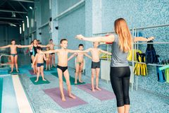 Instructor and group of children doing exercises. Female instructor and group of children doing exercises near a swimming pool. Healthy and happy childhood Stock Image