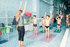 Instructor and group of children doing exercises. Female instructor and group of children doing exercises near a swimming pool. Healthy and happy childhood Stock Images