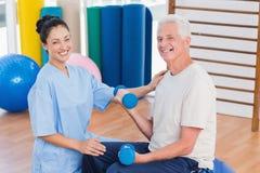 Female instructor with senior man lifting dumbbells. Portrait of female instructor with senior man lifting dumbbells at gym Royalty Free Stock Image
