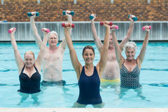 Female instructor with senior swimmers exercising in swimming pool. Portrait of female instructor with senior swimmers exercising in swimming pool Stock Photography