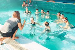 Instructor teaches children how to swim. Female instructor teaches children how to swim. Kids with goggles in water listening trainer. Happy kids in modern sport Stock Photos