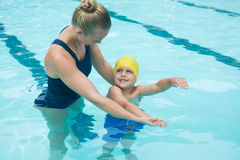 Female instructor training young boy in pool Royalty Free Stock Images