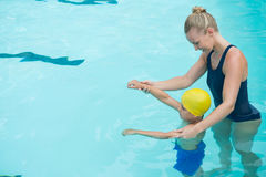 Female instructor training young boy in pool Stock Photos
