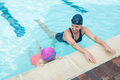 Female instructor training young girl in pool. At leisure center Royalty Free Stock Photo