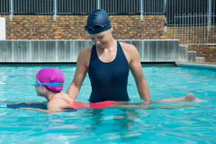 Female instructor training young girl in pool. At leisure center Stock Photo