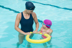 Female instructor training young girl in pool. At leisure center Royalty Free Stock Image