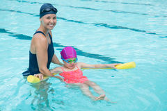 Female instructor training young girl in pool. At leisure center Royalty Free Stock Photography